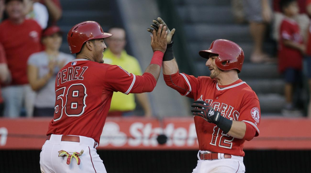 Los Angeles Angels' Johnny Giavotella, right, celebrates his two-run home run with Carlos Perez during the sixth inning of a baseball game against the Oakland Athletics, Wednesday, Sept. 30, 2015, in Anaheim, Calif. (AP Photo/Jae C. Hong)