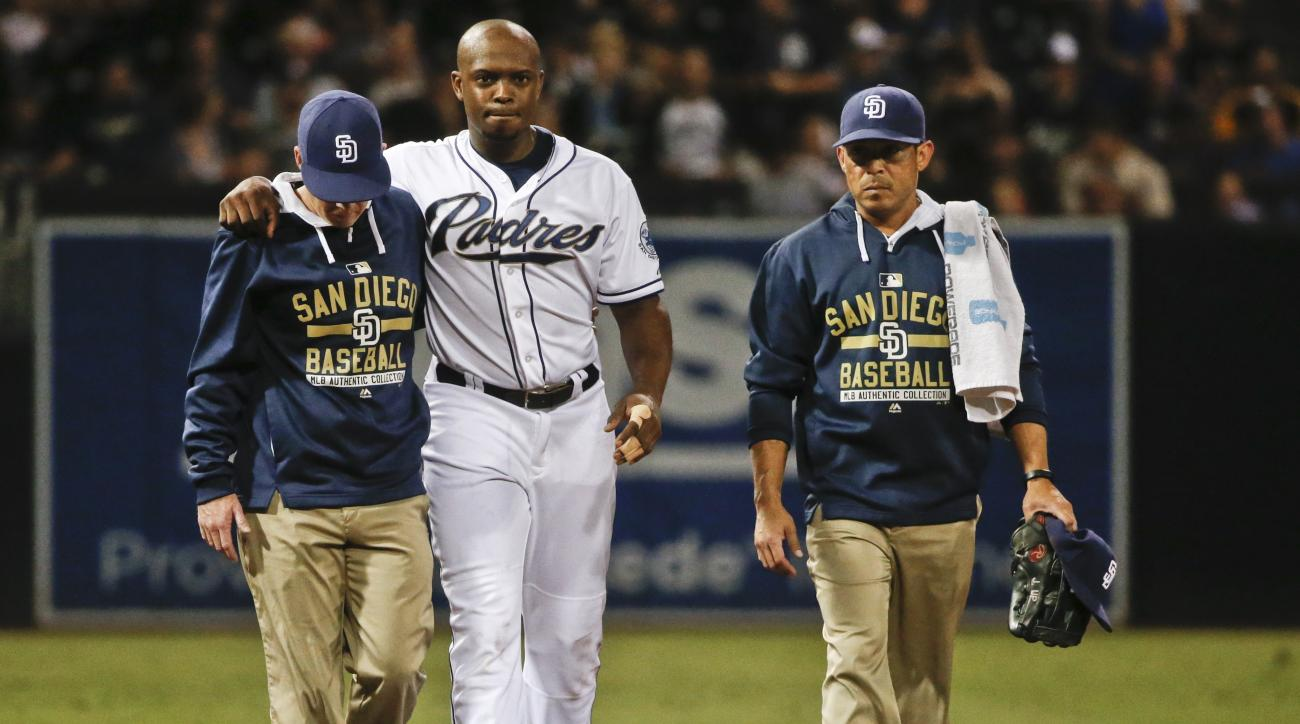 San Diego Padres left fielder Justin Upton helped from the field after being injured crashing into the wall fielding a hit by Milwaukee Brewers' Logan Schafer in the first inning of a baseball game Wednesday, Sept. 30, 2015, in San Diego. (AP Photo/Lenny