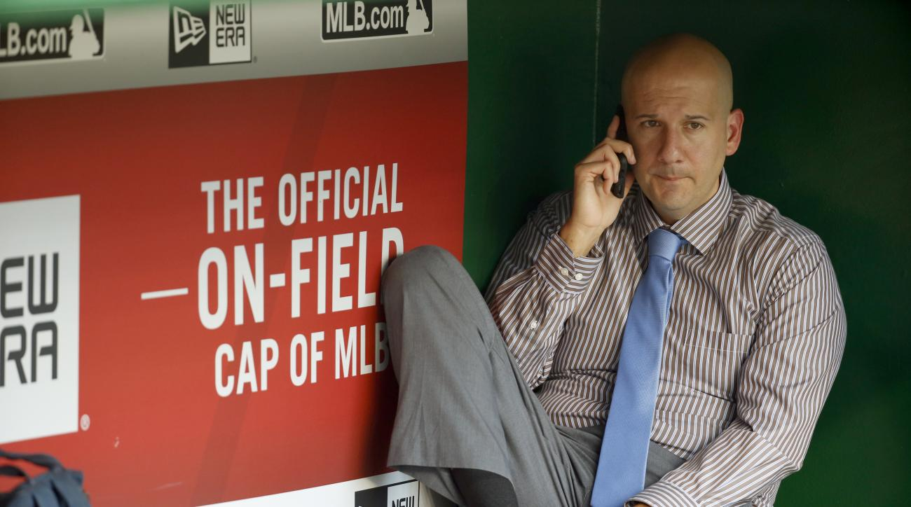 Atlanta Braves assistant general manager and director of pro scouting John Coppolella talks on the phone in the dugout during batting practice before a baseball game against the Washington Nationals at Nationals Park, Friday, Sept. 4, 2015, in Washington.