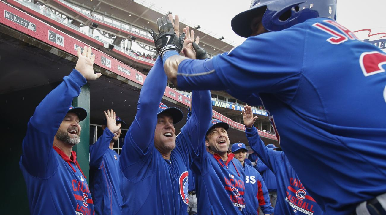The Chicago Cubs dugout celebrates as Austin Jackson, right, returns following his three-run home run off Cincinnati Reds starting pitcher John Lamb in the third inning of a baseball game, Thursday, Oct. 1, 2015, in Cincinnati. (AP Photo/John Minchillo)