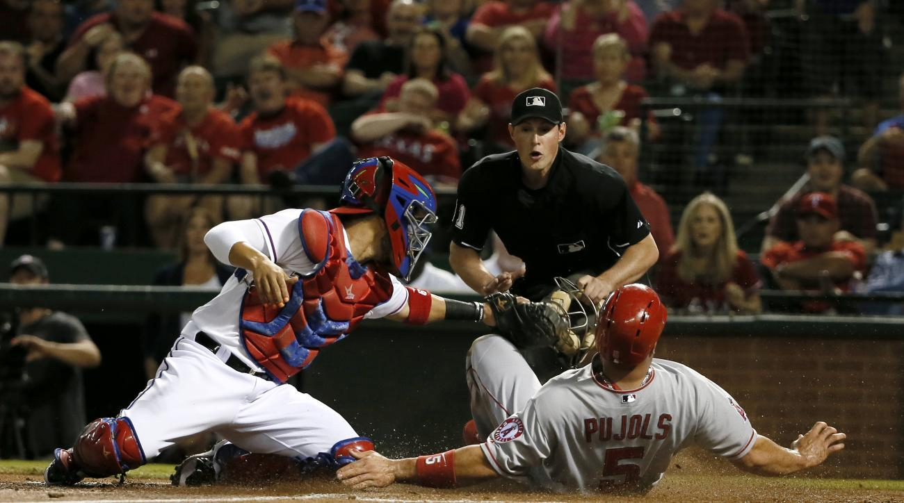 Texas Rangers' Robinson Chirinos is unable to tag out Los Angeles Angels' Albert Pujols (5) who scored on a sacrifice fly by Shane Victorino in the second inning of a baseball game Thursday, Oct. 1, 2015, in Arlington, Texas. Home plate umpire Quinn Wolco