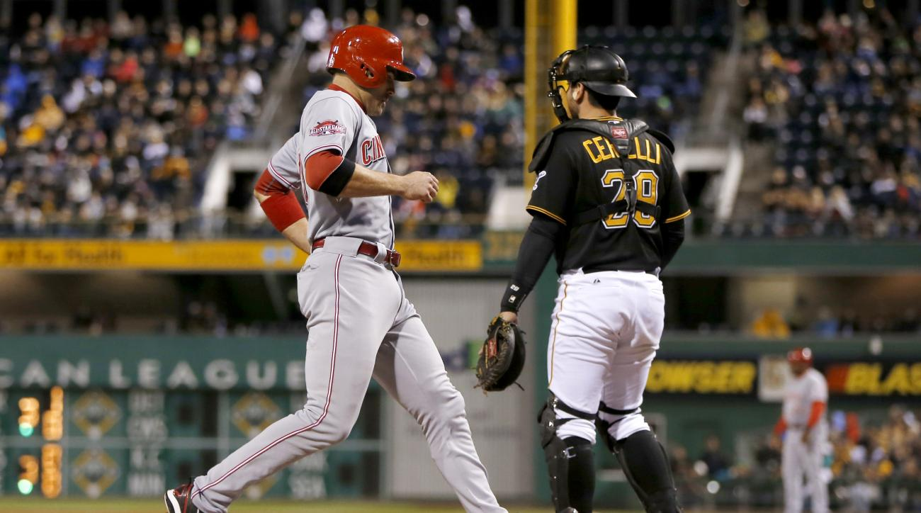 Cincinnati Reds' Joey Votto, left, scores from second behind Pittsburgh Pirates catcher Francisco Cervelli on a double by Jay Bruce in the third inning of a baseball game, Friday, Oct. 2, 2015, in Pittsburgh. (AP Photo/Keith Srakocic)