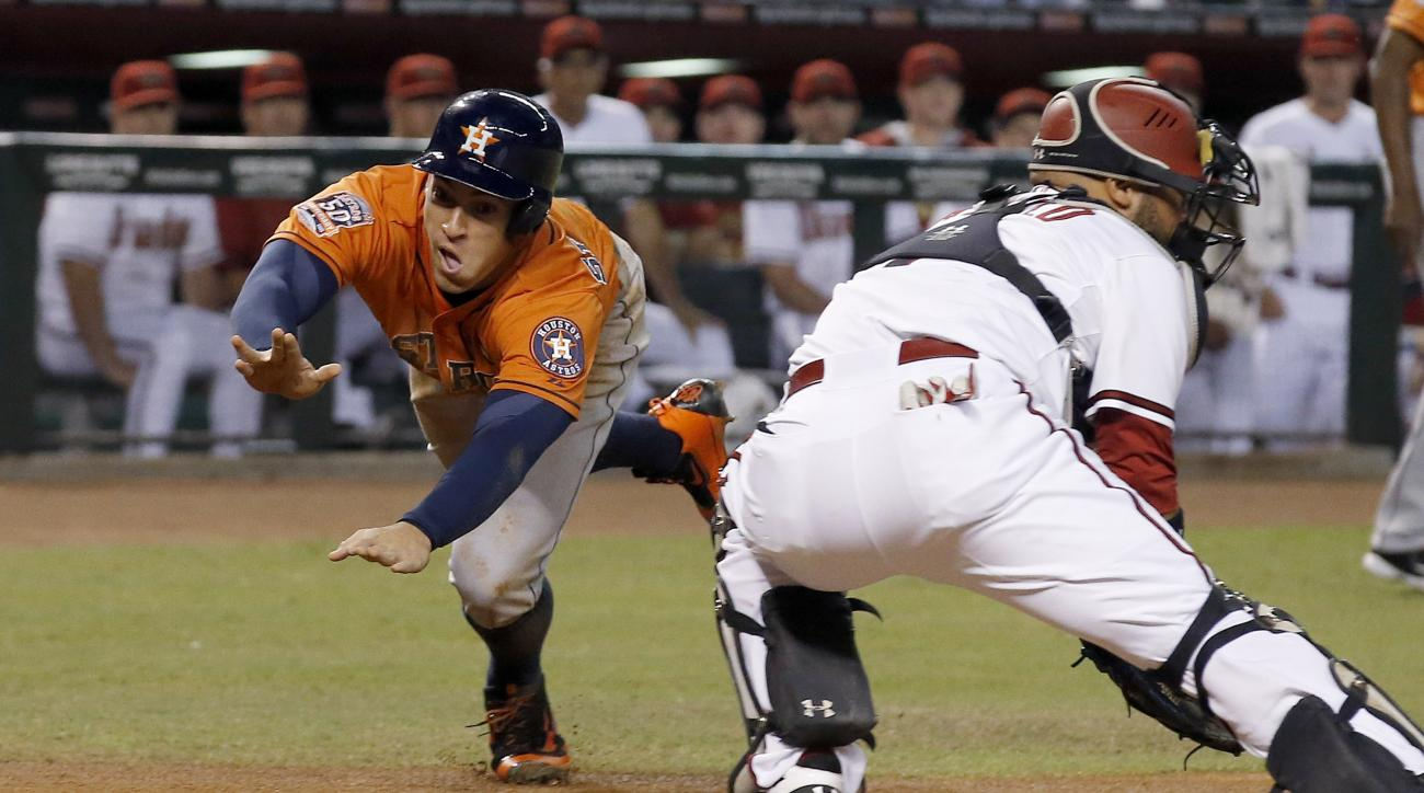 Houston Astros' George Springer, left, dives around Arizona Diamondbacks' Welington Castillo, right, to score a run during the first inning of a baseball game Friday, Oct. 2, 2015, in Phoenix. (AP Photo/Ross D. Franklin)