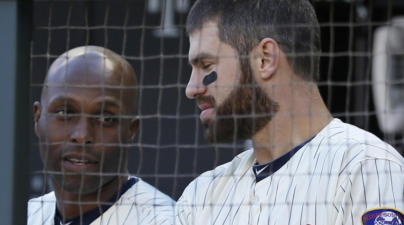 Minnesota Twins' Torii Hunter, left, and Joe Mauer talk in the dugout in the late innings of a baseball game against the Kansas City Royals, Saturday, Oct. 3, 2015, in Minneapolis. The Twins were eliminated from the AL wild-card race after losing 5-1 loss