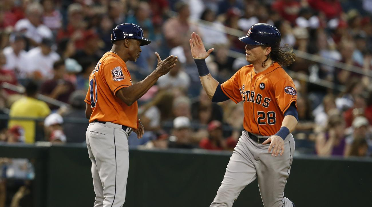 Houston Astros Colby Rasmus (28) celebrates with third base coach Gary Pettis after hitting a solo home run against the Arizona Diamondbacks in the forth inning during a baseball game, Saturday, Oct. 3, 2015, in Phoenix. (AP Photo/Rick Scuteri)