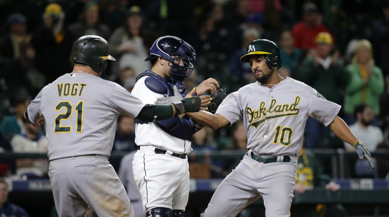 Oakland Athletics' Marcus Semien (10) is greeted at the plate by Stephen Vogt after Semien hit a two-run go-ahead home run to score Vogt in the 13th inning of a baseball game against the Seattle Mariners, Saturday, Oct. 3, 2015, in Seattle. (AP Photo/Ted