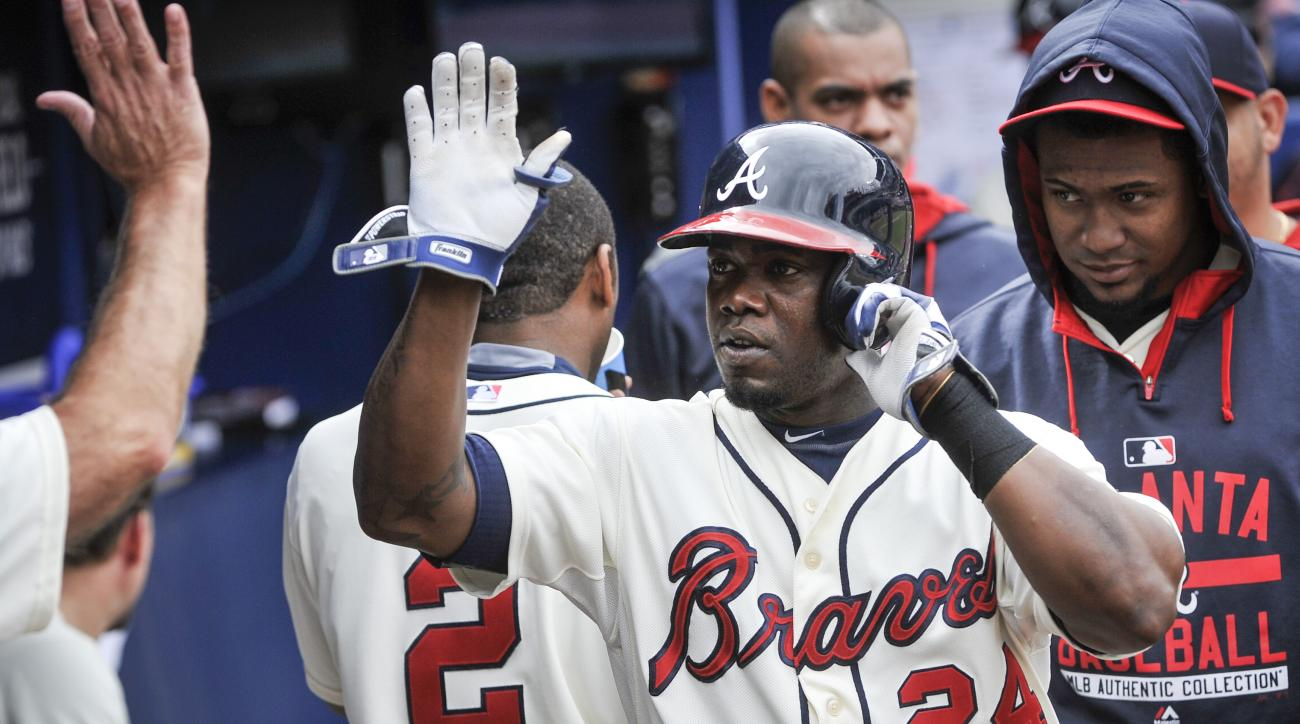 Atlanta Braves' Adonis Garcia (24) celebrates a home run during the fourth inning of the first baseball game of a doubleheader against the St. Louis Cardinals, Sunday, Oct. 4, 2015, in Atlanta. (AP Photo/John Amis)
