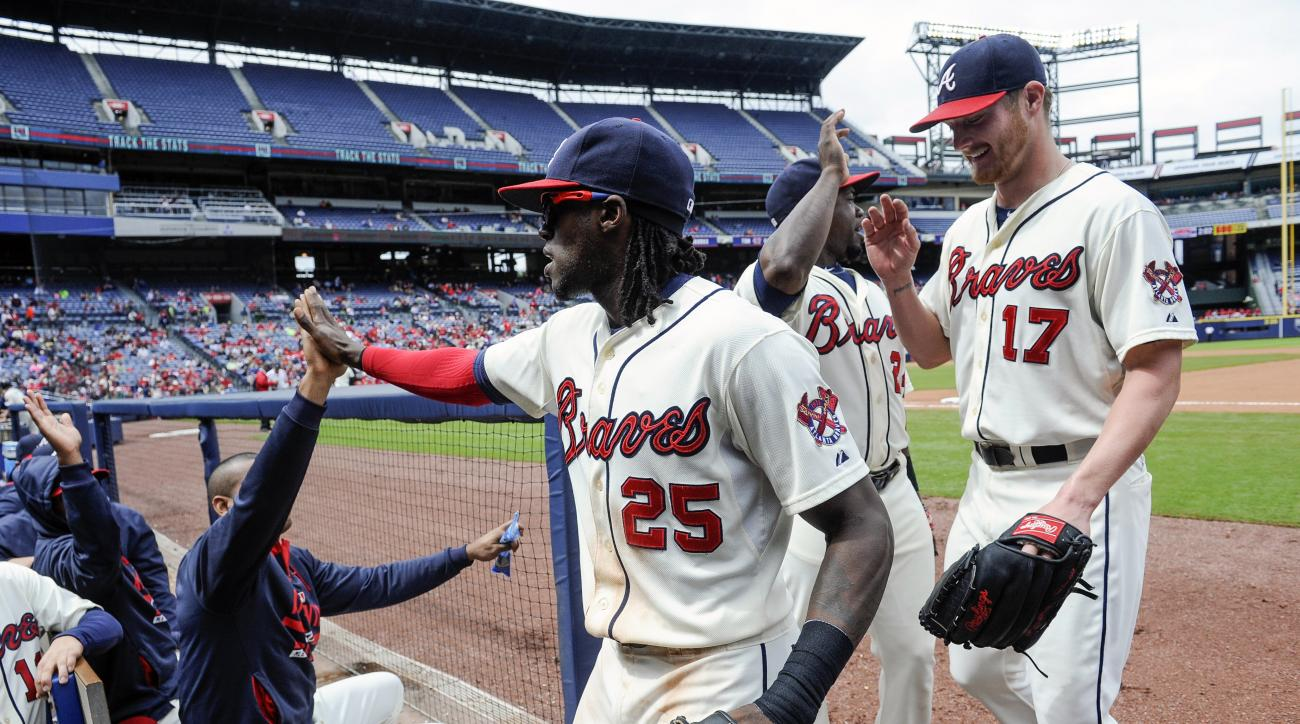 Atlanta Braves center fielder Cameron Maybin (25) is followed by pitcher Shelby Miller (17) as he is congratulated while entering the dugout after catching a fly ball hit by St. Louis Cardinals' Brandon Moss and throwing out Greg Garcia at first to turn a