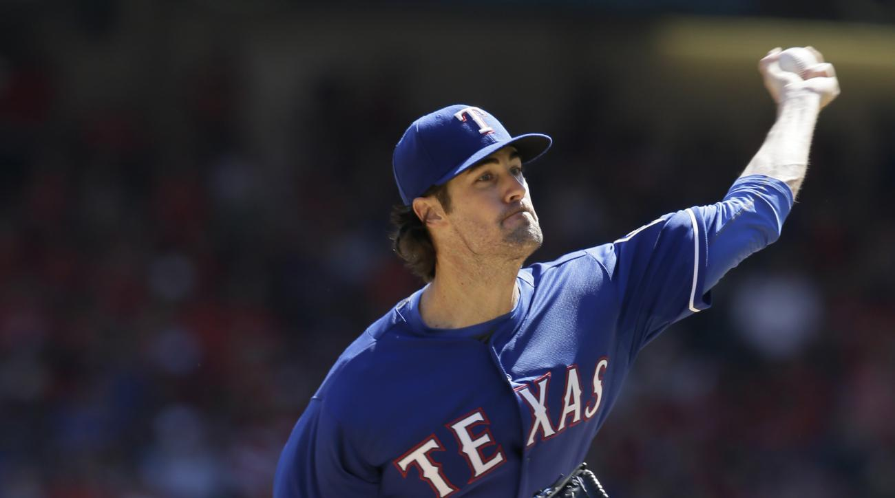 Texas Rangers starting pitcher Cole Hamels throws during the first inning of a baseball game against the Los Angeles Angels in Arlington, Texas, Sunday, Oct. 4, 2015. (AP Photo/LM Otero)