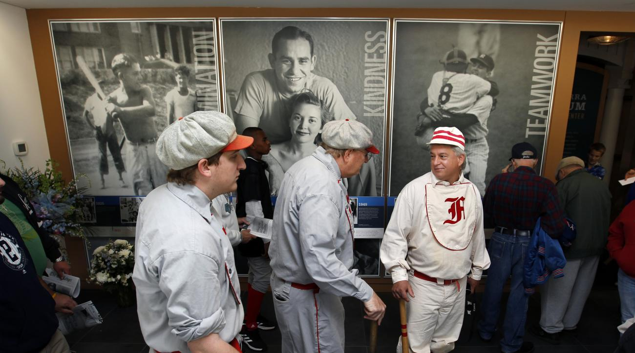 Baseball fans Danny Shaw, left, his father, Brad Shaw, of Manalapan, N.J., and Mark Granieri, of Washington Township, N.J., right, all wear replica 1800s Cincinnati Reds baseball uniforms as they attend a public memorial service at the Yogi Berra Museum f
