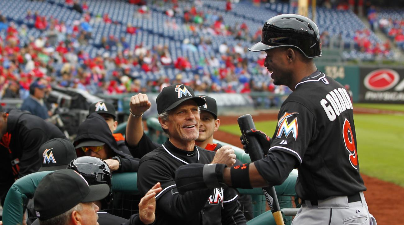 Miami Marlins' Dee Gordon (9) is congratulated in the dugout by teammates after scoring on a double by Justin Bour in the first inning against the Philadelphia Phillies during a baseball game Sunday, Oct. 4, 2015, in Philadelphia. (AP Photo/Rich Schultz)