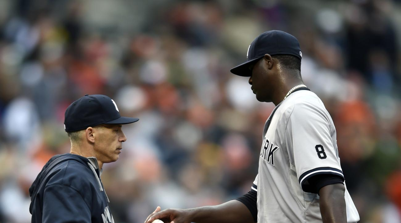 New York Yankees starting pitcher Michael Pineda, right, is taken out of a baseball game by manager Joe Girardi after the Baltimore Orioles scored a run in the fourth inning in Baltimore, Sunday, Oct. 4, 2015. (AP Photo/Gail Burton)