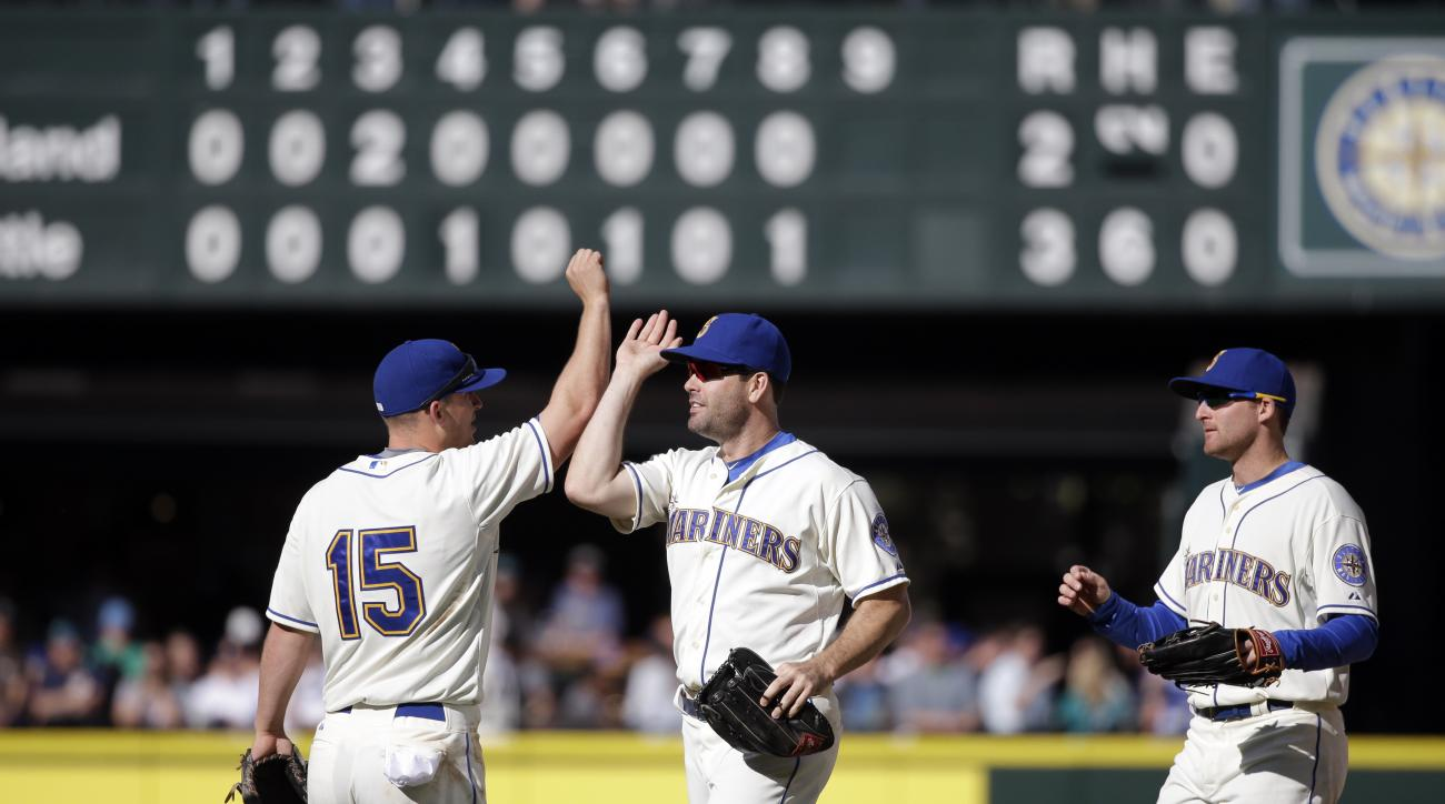 Seattle Mariners' Kyle Seager (15), Seth Smith, and Brad Miller share congratulations after a baseball game Sunday, Oct. 4, 2015, in Seattle. The Mariners won 3-2. (AP Photo/Elaine Thompson)