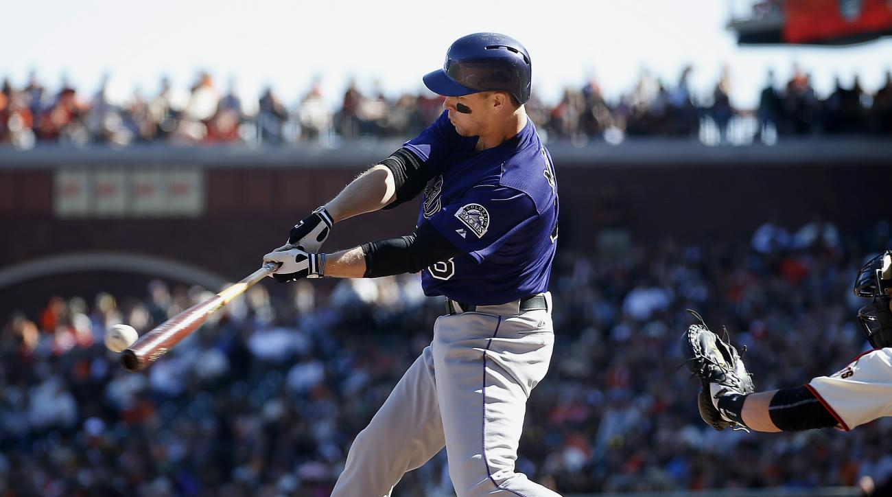 Colorado Rockies' Justin Morneau hits a single to drive in two runs against the San Francisco Giants during the ninth inning of a baseball game, Sunday, Oct. 4, 2015, in San Francisco. (AP Photo/Tony Avelar)