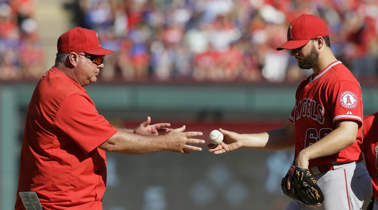 Los Angeles Angels relief pitcher Cam Bedrosian, right, is pulled in the seventh inning by manager Mike Scioscia during a baseball game against the Texas Rangers in Arlington, Texas, Sunday, Oct. 4, 2015. The Rangers won 9-2. (AP Photo/LM Otero)