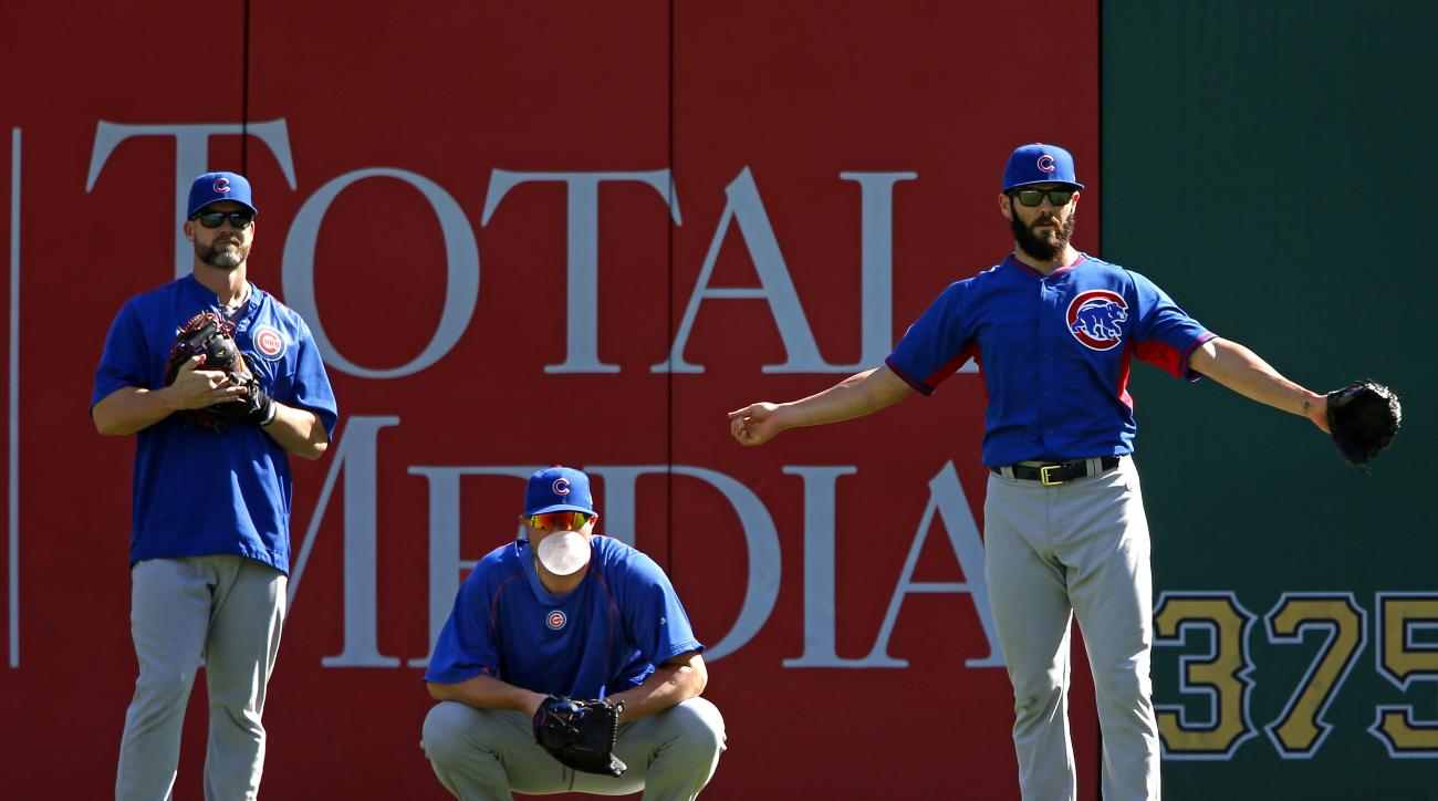 Chicago Cubs starting pitcher Jake Arrieta, right, stands in the outfield with Jon Lester, center, and David Ross on workout day, Tuesday, Oct. 6, 2015, for Wednesday's National League Wild Card baseball game at PNC Park in Pittsburgh. (AP Photo/Gene J. P