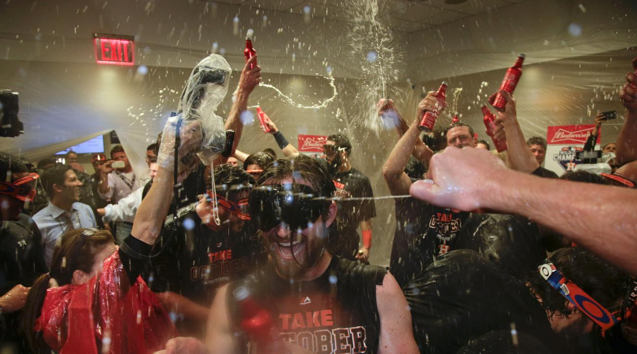 The Houston Astros celebrate in their locker room after defeating the New York Yankees 3-0 in the American League wild card baseball game Tuesday, Oct. 6, 2015, in New York. (AP Photo/Julie Jacobson)