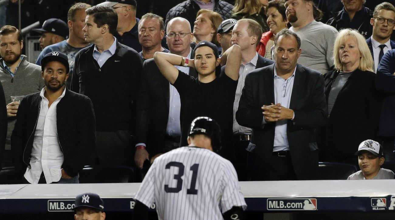 Baseball fans watch as New York Yankees' Greg Bird (31) walks back to the dugout after being called out on strikes with a man on base during the seventh inning of the American League wild card baseball game against the Houston Astros, Tuesday, Oct. 6, 201