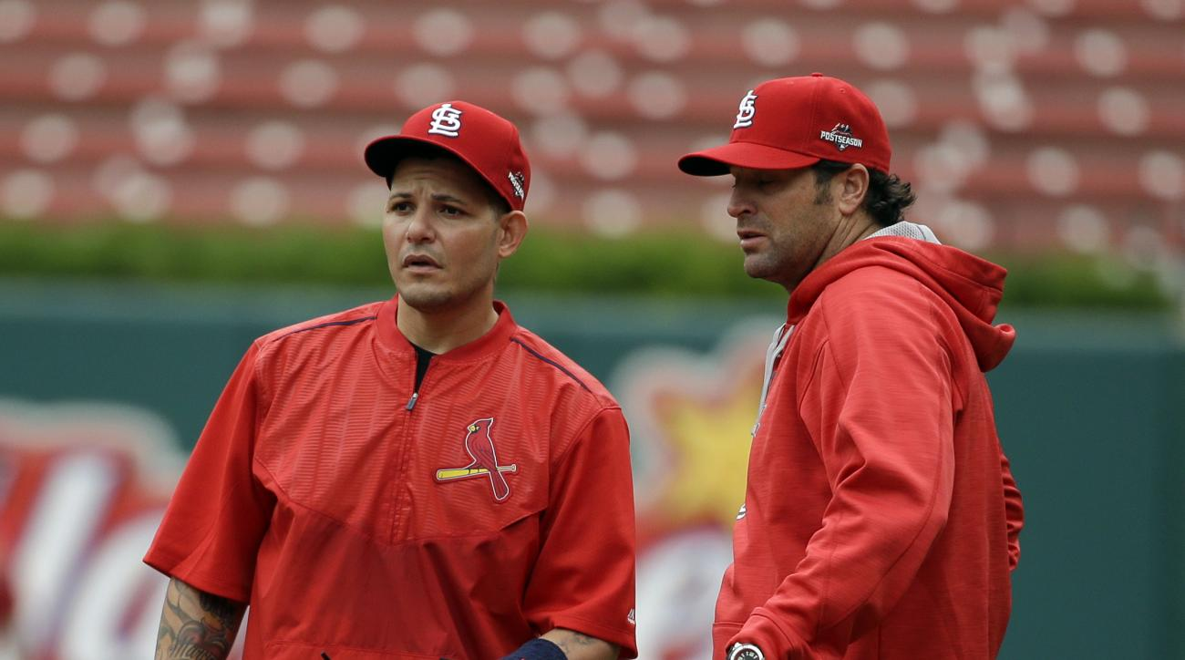 St. Louis Cardinals catcher Yadier Molina, left, talks with manager Mike Matheny during baseball practice on Wednesday, Oct. 7, 2015, in St. Louis. The Cardinals will face either the Pittsburgh Pirates or the Chicago Cubs in Game 1 of the NLDS on Friday i