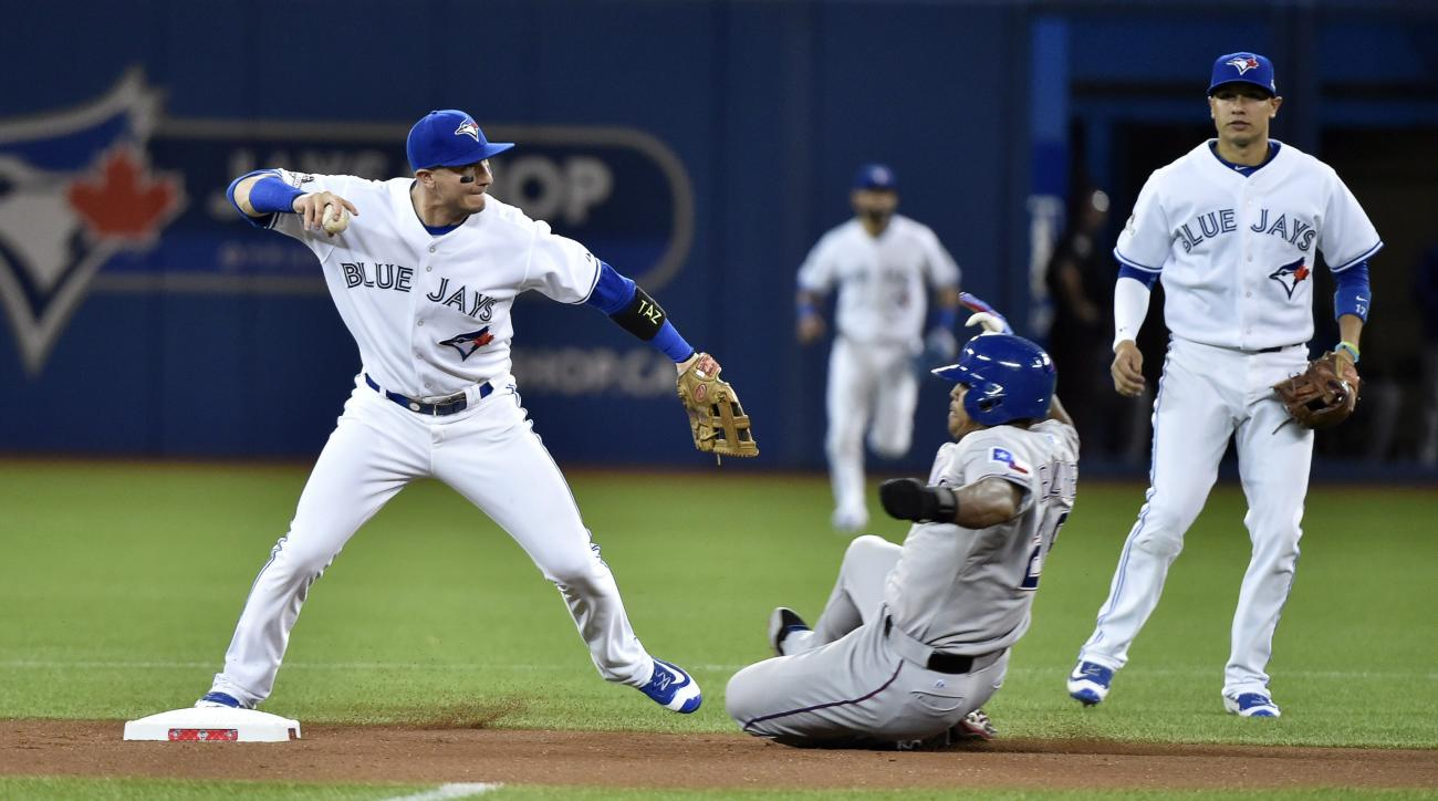 Toronto Blue Jays' shortstop Troy Tulowitzki forces Texas Rangers' Adrian Beltre at second base before throwing to first base for the double play during the first inning in Game 1 of baseballs American League Division Series in Toronto on Thursday, Oct. 8