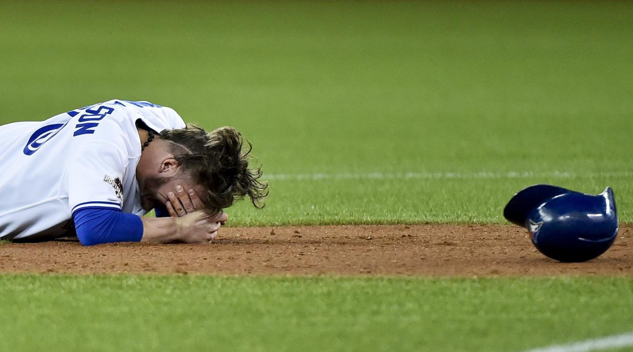 Toronto Blue Jays' Josh Donaldson rests after a collision during a force out at second base by Texas Rangers' Rougned Odor during the fourth inning of Game 1 of the American League Division Series in Toronto on Thursday, Oct. 8, 2015. Texas won 5-3. (Nath
