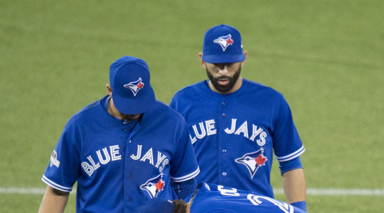 Toronto Blue Jays' Brett Cecil, right, rests with an injury next to teammates Chris Colabello, left, and Jose Bautista during the eighth inning of Game 2 of the American League Division Series against the Texas Rangers in Toronto, Friday, Oct. 9, 2015. (D