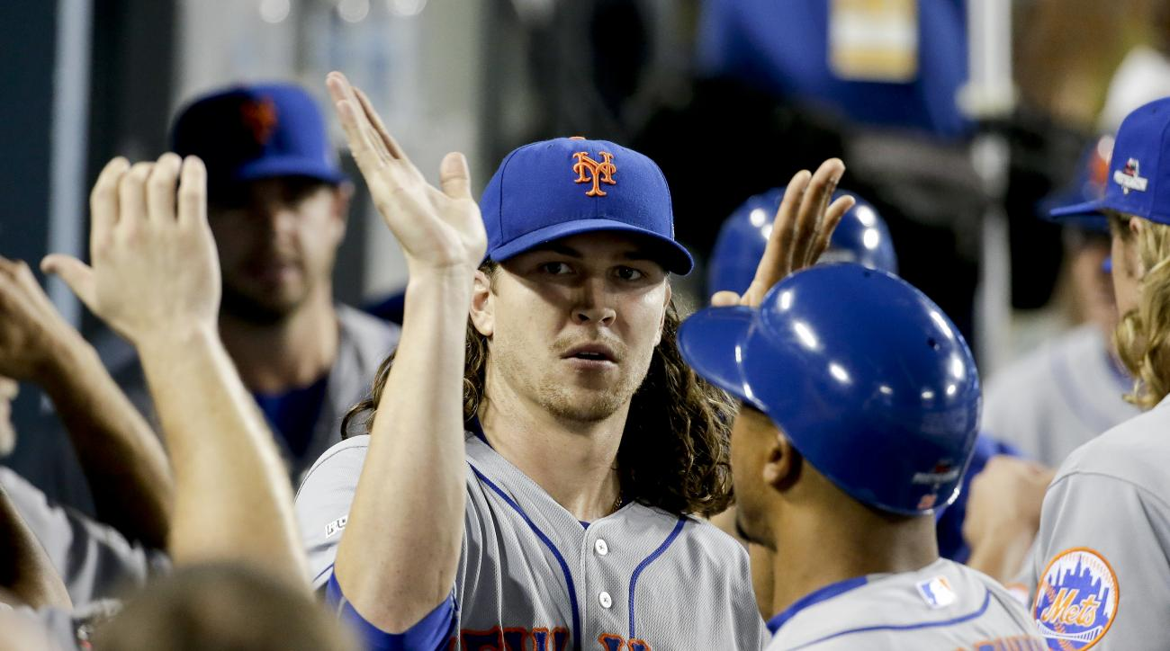 New York Mets starting pitcher Jacob deGrom celebrates in the dugout the end of the seventh inning against the Los Angeles Dodgers during Game 1 of baseball's National League Division Series, Friday, Oct. 9, 2015 in Los Angeles. (AP Photo/Gregory Bull)