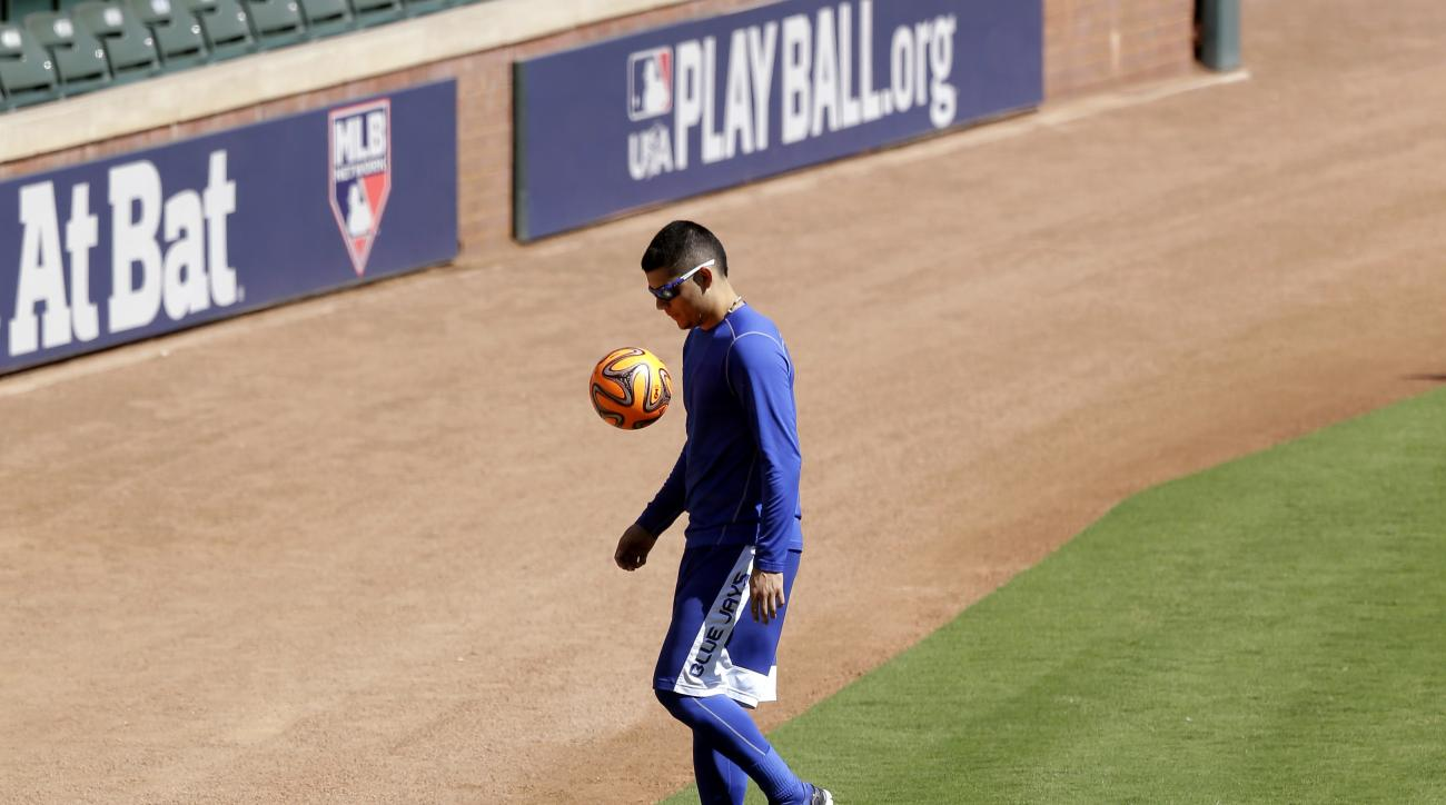 Toronto Blue Jays' Roberto Osuna plays with a soccer ball as he waits to begin an American League Division Series baseball practice, Saturday, Oct. 10, 2015, in Arlington, Texas. The Blue Jays will face the Texas Rangers in game 3 Sunday. (AP Photo/Eric G