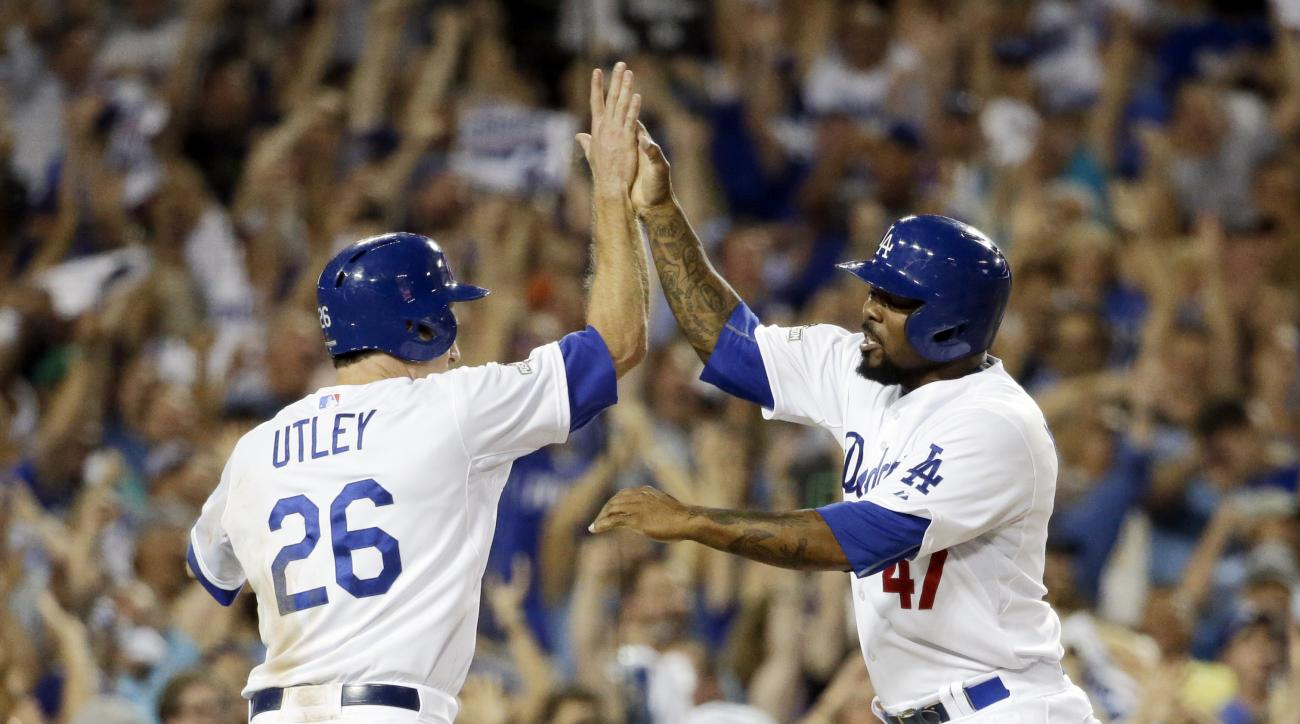 Los Angeles Dodgers' Chase Utley, left, and Howie Kendrick celebrates after scoring on a hit by Adrian Gonzalez during the seventh inning in Game 2 of baseball's National League Division Series against the New York Mets, Saturday, Oct. 10, 2015 in Los Ang