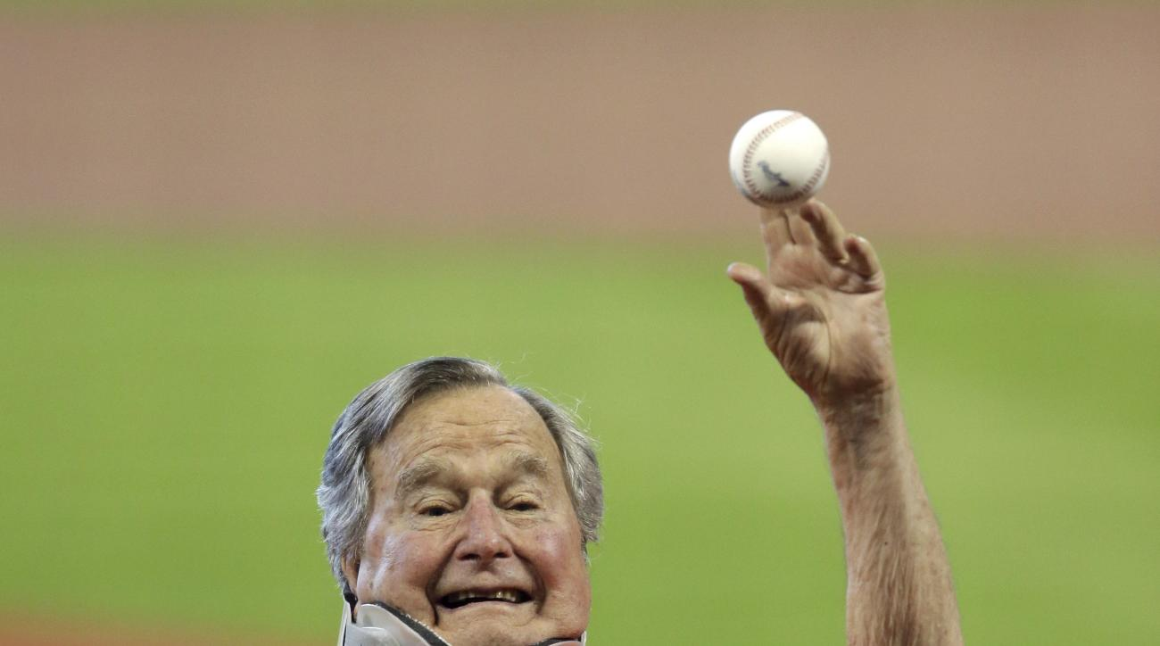 Former President George H.W. Bush throws out the ceremonial first pitch to Houston Astros' Jed Lowrie before Game 3 of baseball's American League Division Series against the Kansas City Royals Sunday, Oct. 11, 2015, in Houston. (AP Photo/David J. Phillip)
