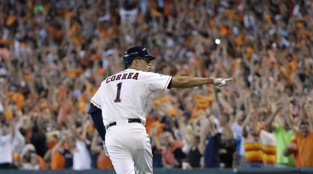 Houston Astros' Carlos Correa (1) points to teammates as he rounds the bases after hitting a solo home run against the Kansas City Royals in the seventh inning during Game 4 of baseball's American League Division Series, Monday, Oct. 12, 2015, in Houston.