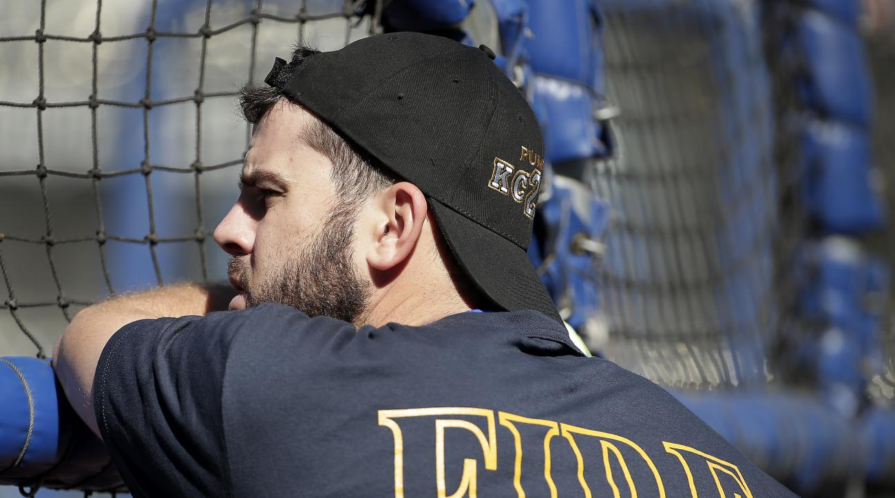 Kansas City Royals' Mike Moustakas wears Kansas City Fire Department apparel as he waits to bat during baseball practice Tuesday, Oct. 13, 2015, in Kansas City, Mo. The Royals face the Astros in Game 5 of the ALDS Wednesday. Moustakas was waring the shirt