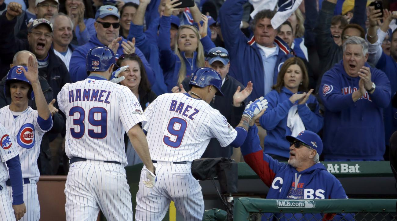 Chicago Cubs manager Joe Maddon, right, congratulates Javier Baez (9) for his three-run home run against the St. Louis Cardinals during the second inning of Game 4 in baseball's National League Division Series, Tuesday, Oct. 13, 2015, in Chicago. At left