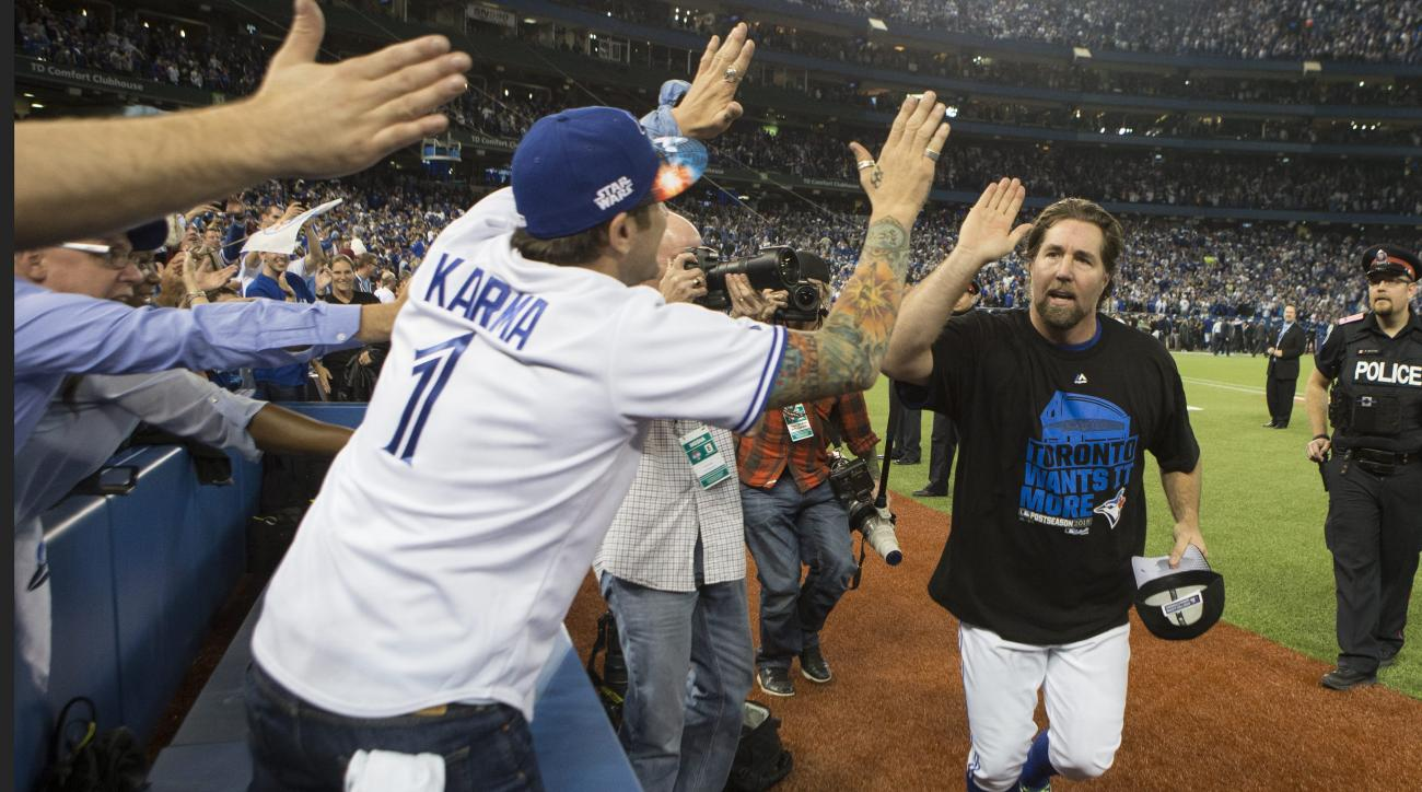 Toronto Blue Jays' R.A. Dickey celebrates with fans after winning  Game 5 of baseball's American League Division Series against the Texas Rangers, Wednesday, Oct. 14, 2015, in Toronto. The Blue Jays clinched their first trip to the American League Champio