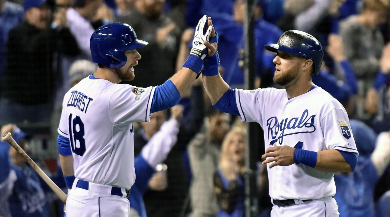 Kansas City Royals' Alex Gordon, right, is congratulated by teammate Ben Zobrist after scoring the first run against the Toronto Blue Jays during the third inning of Game 1 of baseball's American League Championship Series in Kansas City, Mo., Friday, Oct