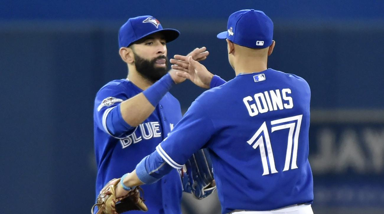 Toronto Blue Jays' Jose Bautista and Ryan Goins (17) celebrate their 11-8 win over the Kansas City Royals in Game 3 of baseball's American League Championship Series on Monday, Oct. 19, 2015, in Toronto. (Nathan Denette/The Canadian Press via AP) MANDATOR