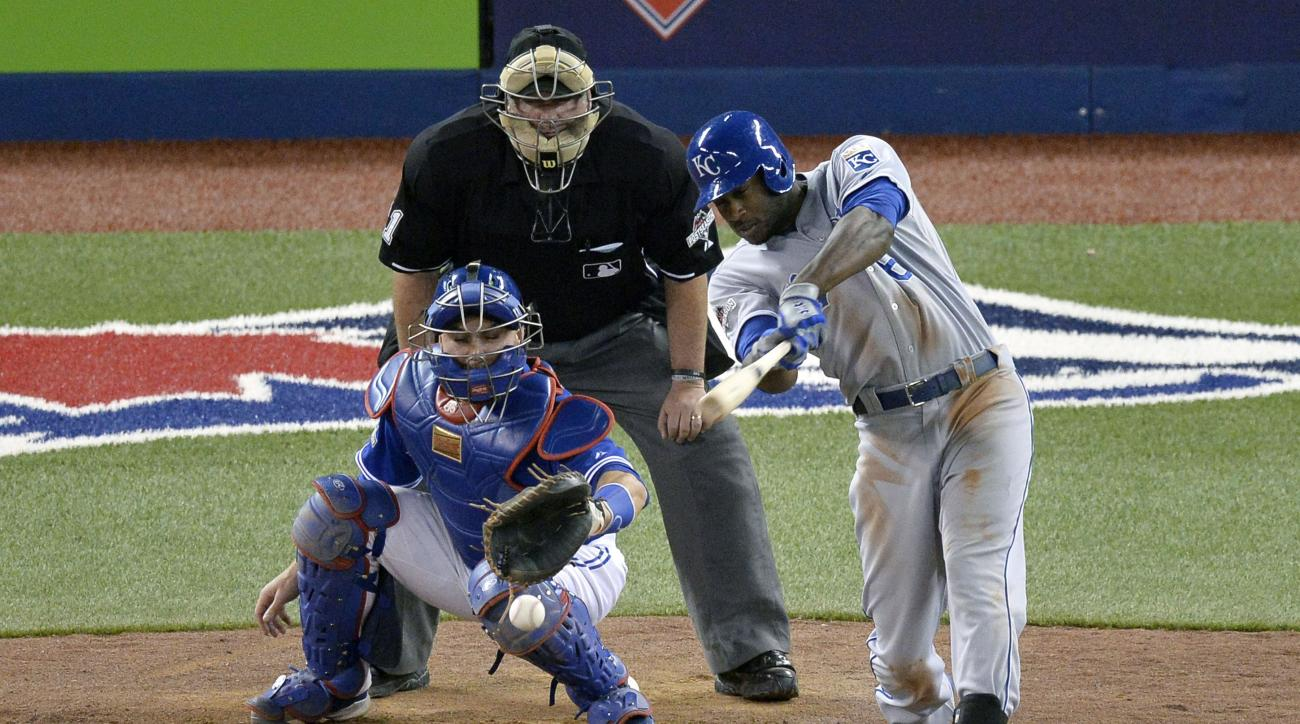 Kansas City Royals'  Lorenzo Cain hits a two-run single as Toronto Blue Jays' catcher Russell Martin looks on during the eighth inning in Game 4 of baseball's American League Championship Series on Tuesday, Oct. 20, 2015, in Toronto. (Chris Young/The Cana