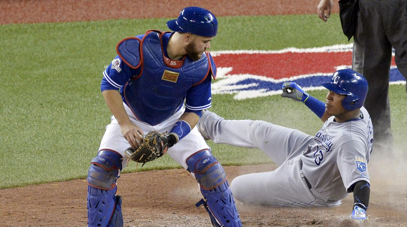 Kansas City Royals' Salvador Perez, right, looks up at Toronto Blue Jays' catcher Russell Martin as he slides into home to score off a sacrifice fly from Alcides Escobar during the seventh inning in Game 4 of baseball's American League Championship Series