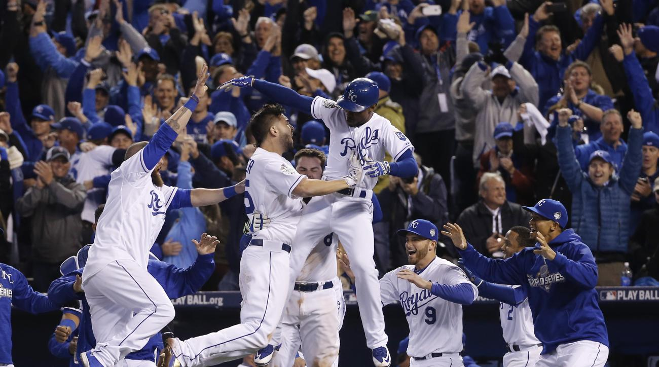 Kansas City Royals celebrate after Alcides Escobar (2) scored on a sacrifice fly by Eric Hosmer during the 14th inning of Game 1 of the Major League Baseball World Series against the New York Mets Wednesday, Oct. 28, 2015, in Kansas City, Mo.  (AP Photo/M