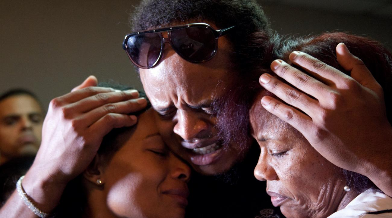 Kansas City Royals player Edinson Volquez, center, embraces his sister Wendy Volquez, left, and mother Ana Ramirez as they stand next to the body of his father Daniel Volquez during his wake at a funeral home in Santo Domingo, Dominican Republic, Wednesda