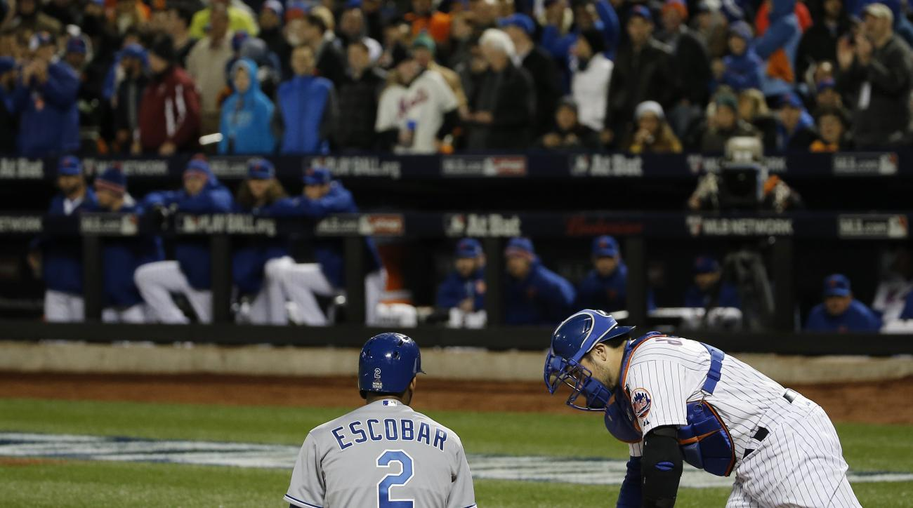 Kansas City Royals' Alcides Escobar (2) sits on the infield after being nearly hit by a pitch from New York Mets pitcher Noah Syndergaard during the first inning of Game 3 of the Major League Baseball World Series Friday, Oct. 30, 2015, in New York. Right