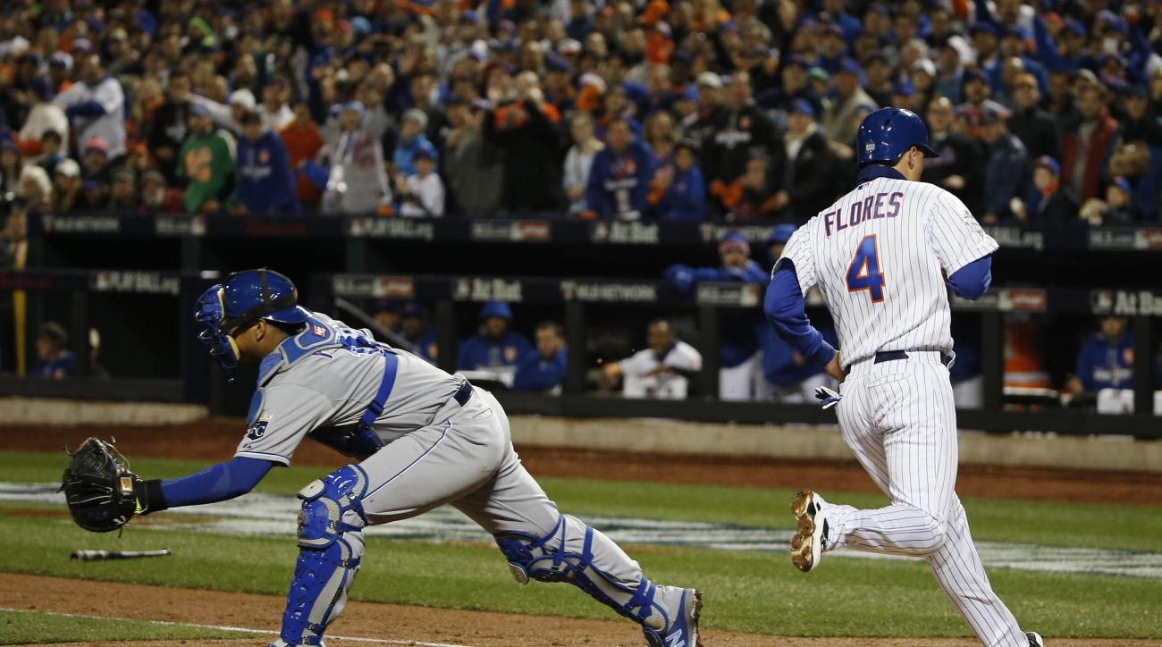 Kansas City Royals catcher Salvador Perez waits for the throw as New York Mets' Wilmer Flores (4) scores on a sacrifice fly during the third inning of Game 4 of the Major League Baseball World Series Saturday, Oct. 31, 2015, in New York. (AP Photo/Matt Sl