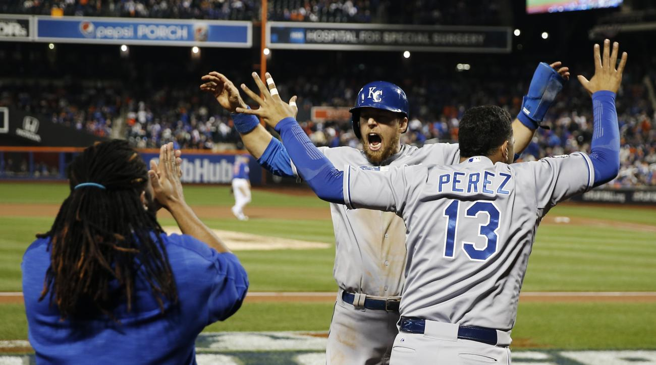 Kansas City Royals' Ben Zobrist (18) celebrates with Salvador Perez after scoring during the 12th inning of Game 5 of the Major League Baseball World Series Monday, Nov. 2, 2015, in New York. (AP Photo/Matt Slocum)