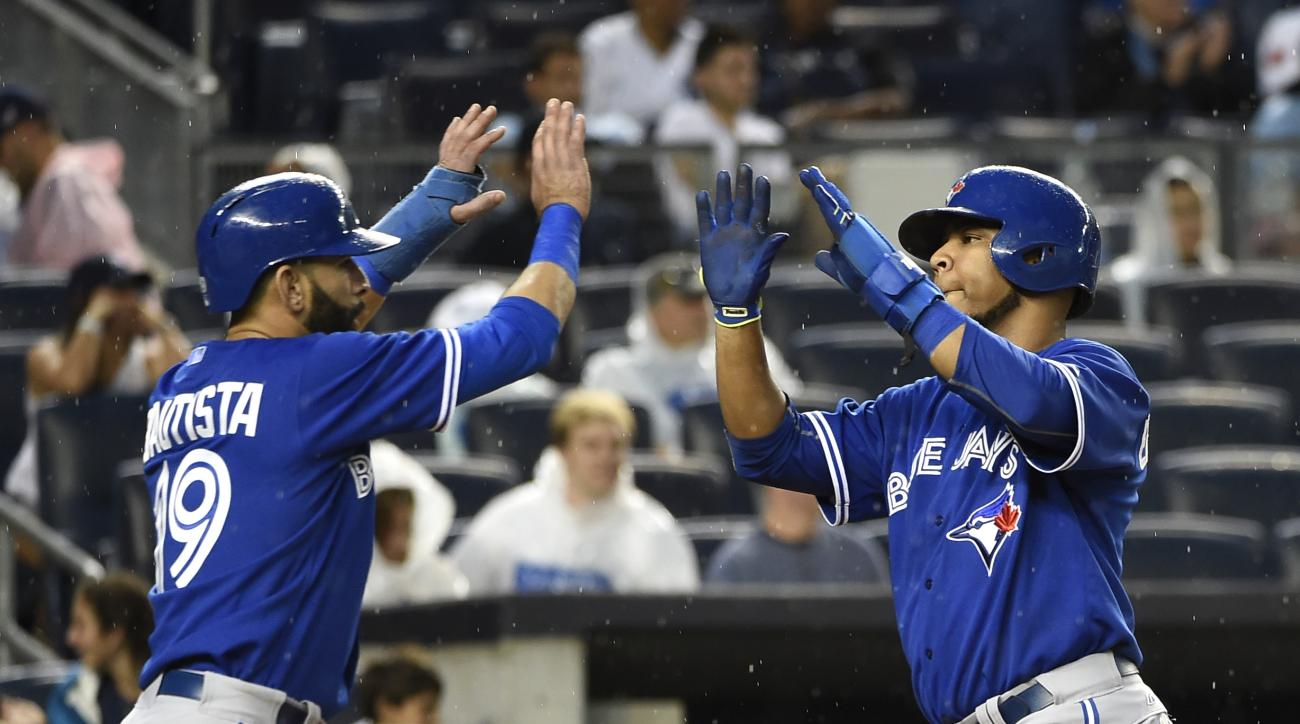 Toronto Blue Jays' Jose Bautista (19) and  Edwin Encarnacion high five at home plate after scoring on Russell Martin's double off of New York Yankees starting pitcher Ivan Nova in the second inning in Game 2 of a doubleheader baseball game at Yankee Stadi