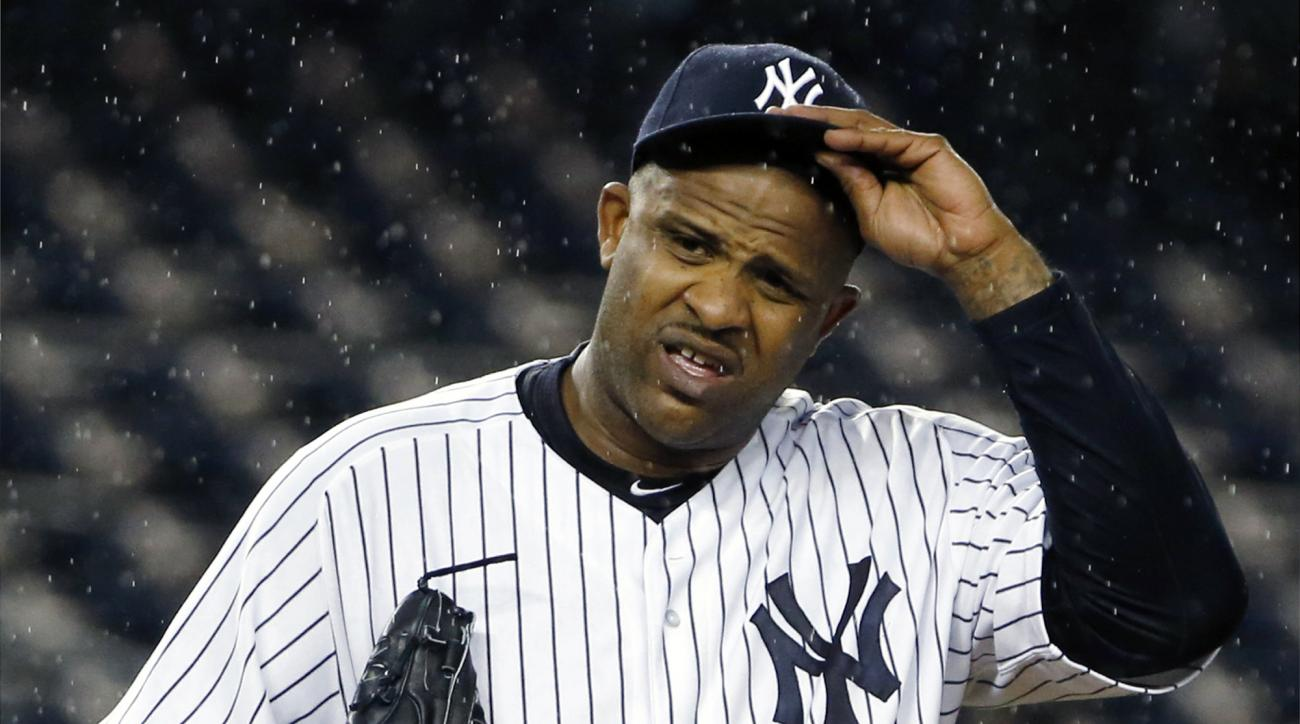 "FILE - In this Oct. 1, 2015, file photo, New York Yankees starting pitcher CC Sabathia (52) struggles with his cap in the rain during the first inning of a baseball game against the Boston Red Sox in New York. Sabathia says he had ""no other option"" than t"