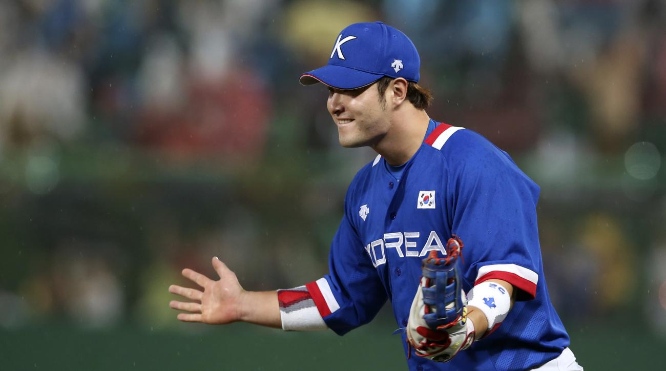 South Korea's first baseman Park Byung-ho celebrates just after his team beat Taiwan 6-3 in their baseball gold medal game at the 17th Asian Games Sunday, Sept. 28, 2014 in Incheon, South Korea. Others are catcher Kang Min-ho and coach Cho Kye-hyun (71).