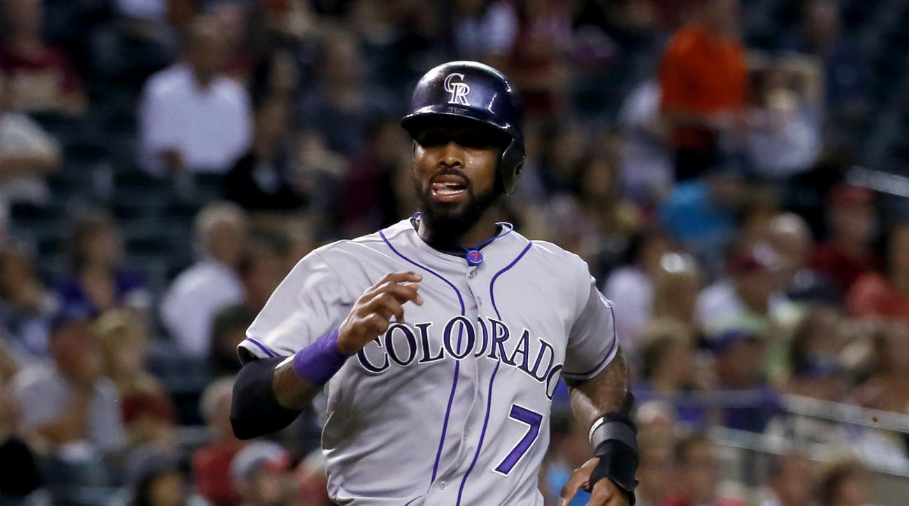 Colorado Rockies' Jose Reyes (7) scores on an RBI base hit by teammate DJ LeMahieu as Arizona Diamondbacks catcher Welington Castillo waits for the throw during the first inning of a baseball game, Thursday, Oct. 1, 2015, in Phoenix. (AP Photo/Matt York)