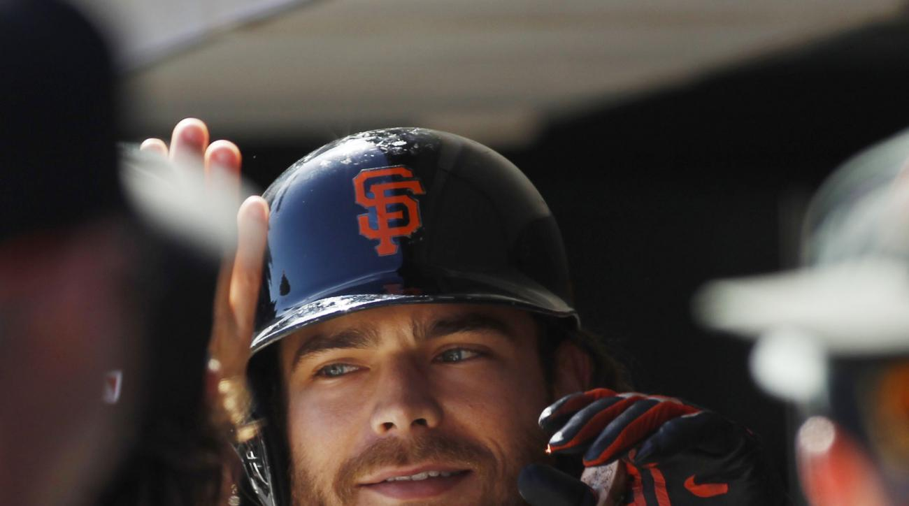 San Francisco Giants' Brandon Crawford smiles in the dugout after hitting a home run against the Colorado Rockies during the fourth inning of a baseball game, Saturday, Oct. 3, 2015, in San Francisco.  (AP Photo/George Nikitin)