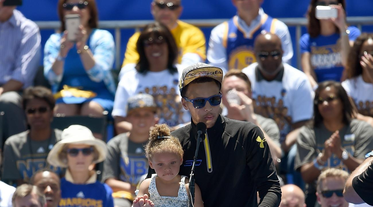OAKLAND, CA - JUNE 19:  Stephen Curry #30 of the Golden State Warriors holds his daughter Riley Curry while he talks to the fans as they celebrate the Warriors 2015 NBA Championship at The Henry J. Kaiser Convention Center during thier Victory Parade and