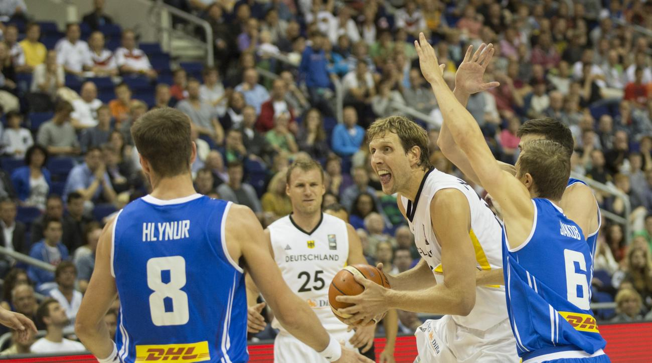 Germany's Dirk Nowitzki, center, holds the ball as he challenge for the ball with  Iceland's Hlynur Baeringsson, left and Iceland's Jakob Sigurdarson, right, during the EuroBasket European Basketball Championship group B match between Germany and Iceland